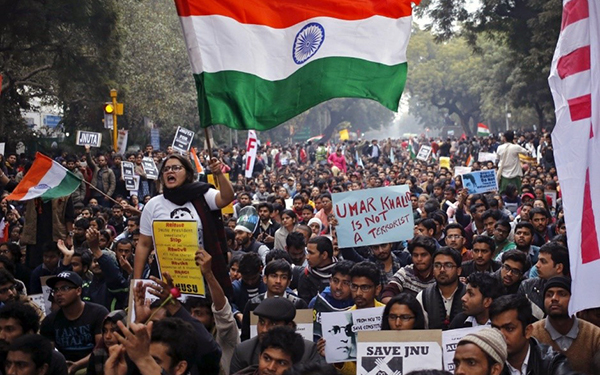 large crowd of protesters holding signs and waving flags in India