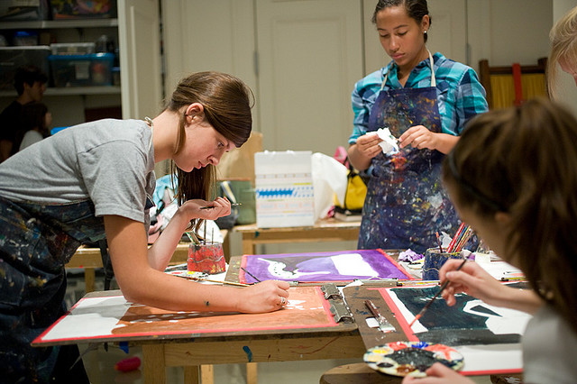 3 girls covered in paint working on art projects in art class
