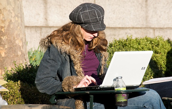 young hip girl sitting outside working on laptop