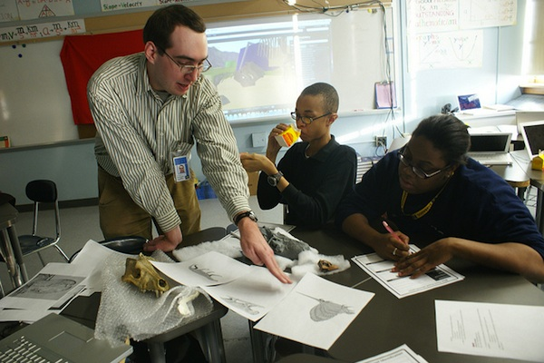 teaching helping students with art project in classroom