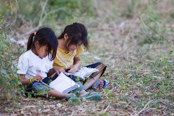 2 young girls sitting in grass woods outside reading school books