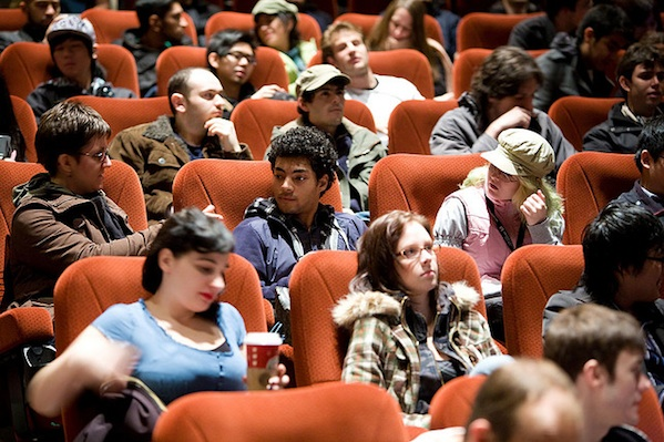 students sitting in theater seats waiting for presentation