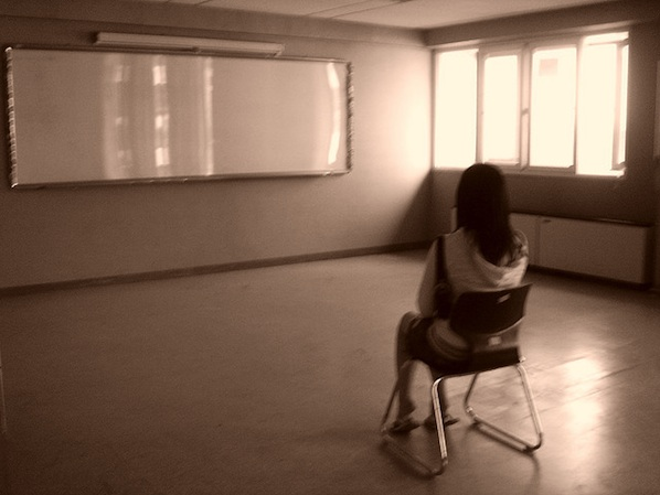1 female student sitting alone in empty classroom
