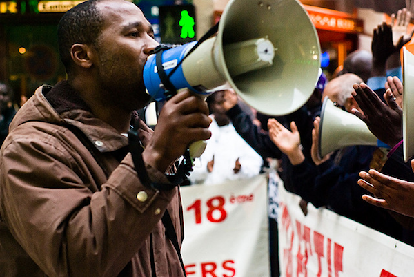black man speaking into bull horn at rally