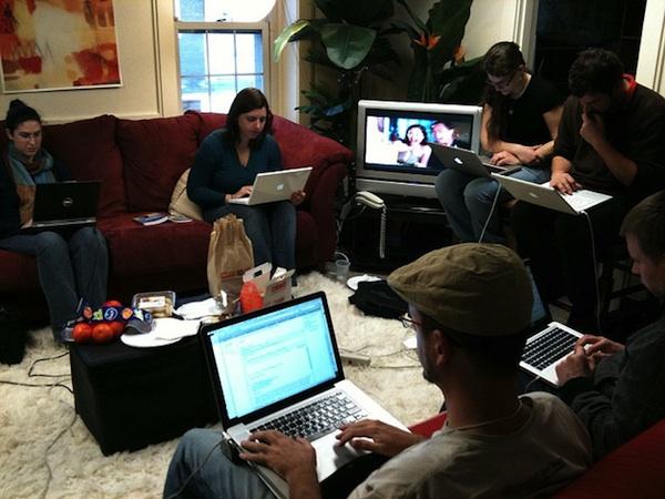people working on laptops in home livingroom