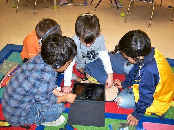 4 little boys sitting on classroom floor all working on ipad with headphones
